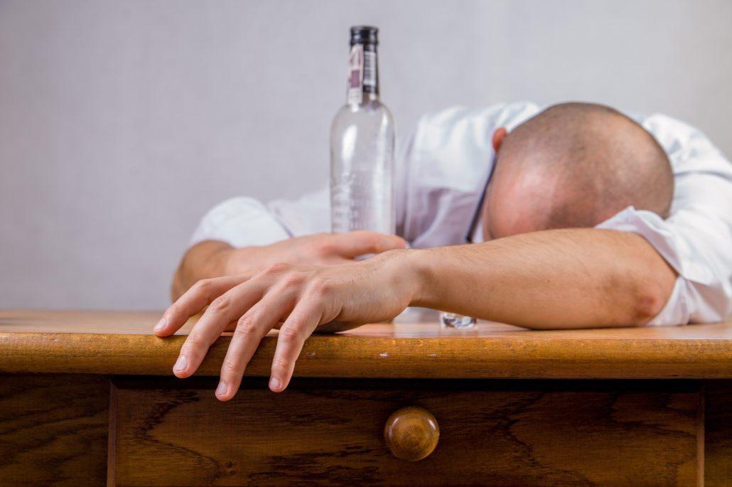 MPU Vorbereitung Wolff - Mann am Tisch und Alkohol Flasche